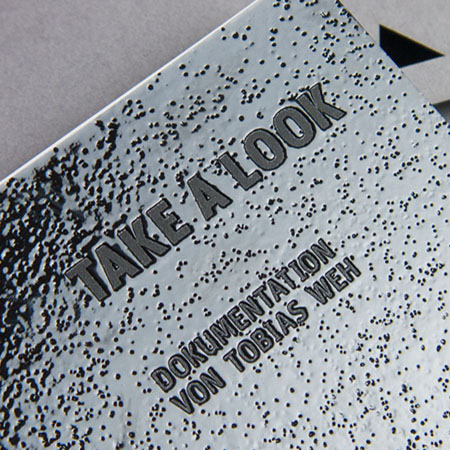 The cover is made out of black cardboard and printed with transparent varnish.